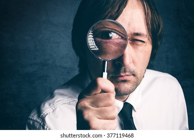 Businessman with magnifying glass, tax inspector doing financial auditing or consultancy, retro toned, selective focus