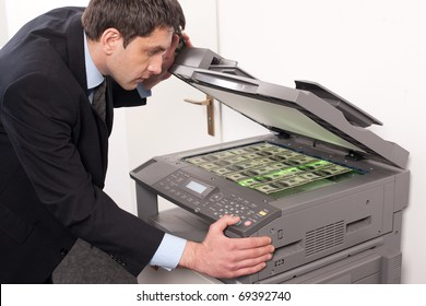 Businessman make false money on copy machine in office