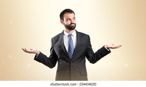 Businessman making a balance gesture over ocher background