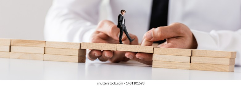 Businessman making a bridge between two stacks of wooden pegs for another businessman to walk safely across in a conceptual image.