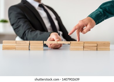Businessman making a bridge of wooden blocks for his partner to walk across in a conceptual image.