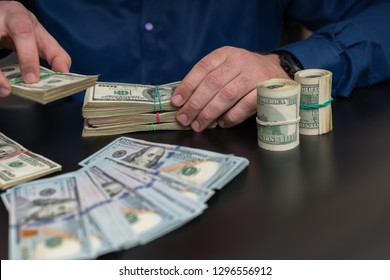 Businessman making a cash payment or offering a bribe handing over stacks of 100 dollar bills across a table in a close up on the hands