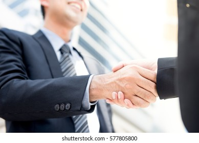 Businessman making handshake with a businesswoman - greeting, dealing, merger and acquisition concepts