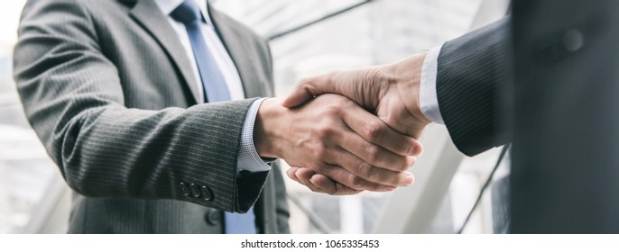 Businessman making handshake with partner - greeting, dealing, merger and acquisition concepts, panoramic banner