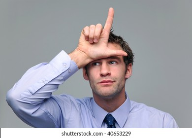 Businessman making a loser gesture with his hand