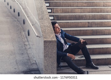Businessman making mistake about financial business. Exhausted and tired worker surrendering to fatigue working with headache sit down on the stairs,