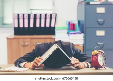 Businessman making mistake about financial business.Exhausted and tired worker surrendering to fatigue working and sleepy worker on desk with laptop on head after late night work at office.Overworking
