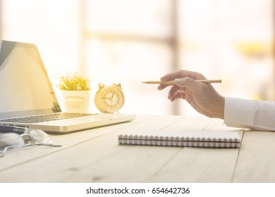 Businessman making notes at the office meeting with computer laptop and glasses.