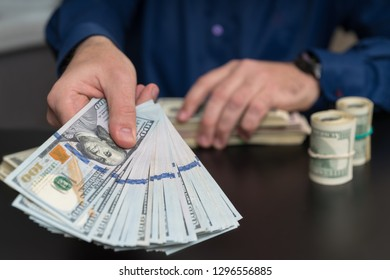 Businessman making a payment or offering a bribe in a finance or corruption concept holding out a handful of dollar bills