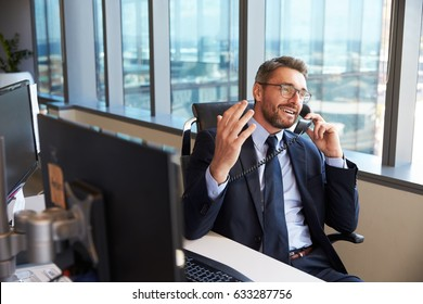 Businessman Making Phone Call Sitting At Desk In Office