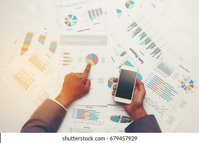 Businessman making presentation and discussion during meeting. Marketing and exploring market data for organization development and market sharing with his colleagues, hand holding mobile phone.