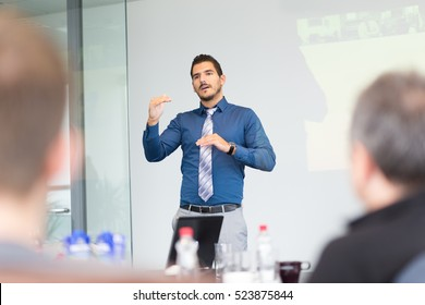 Businessman making a presentation at office. Business executive delivering a presentation to his colleagues during meeting or in-house business training, explaining new business concept and strategy.