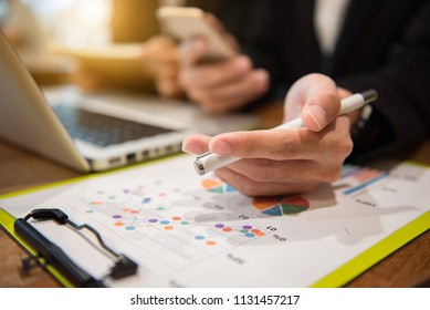 Businessman making presentation on office table with smart phone and laptop computer and graph business with social network diagram and business strategy digital layer effect at the office