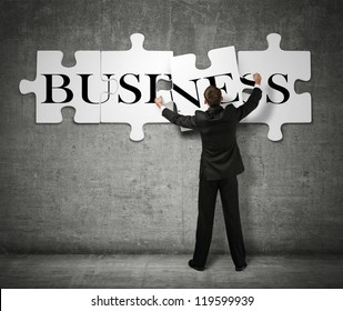 Businessman making a puzzle on the wall with the word Business