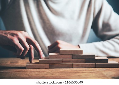 businessman making a pyramid with empty wooden cubes