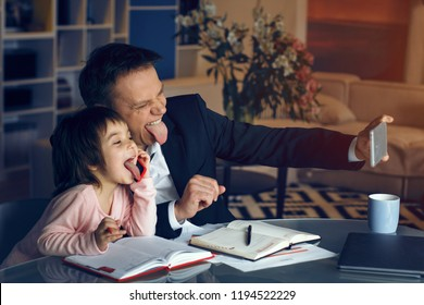 Businessman making selfie with little daughter. Little relax from business at home.