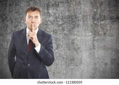 businessman making silence gesture on cement background