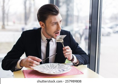 businessman male eating his money, concept. eats dollars. handsome businessman makes a lot of money