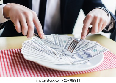 businessman male eating his money, concept. eats dollars.