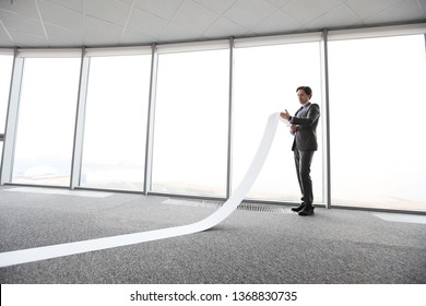 Businessman or male lawyer unrolling and reading long paper list in office
