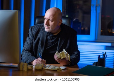 Businessman. A man is counting his money. Bald man in a strict suit. Bundles of money in hand. Business planning. Finance. Calculation of money. Mature man.