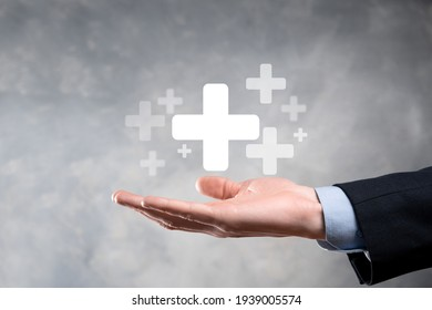Businessman, man hold in hand offer positive thing such as profit, benefits, development, CSR represented by plus sign.The hand shows the plus sign.