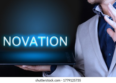 Businessman, man holds in his hand a tablet with a neon word, NOVATION text. Business concept.