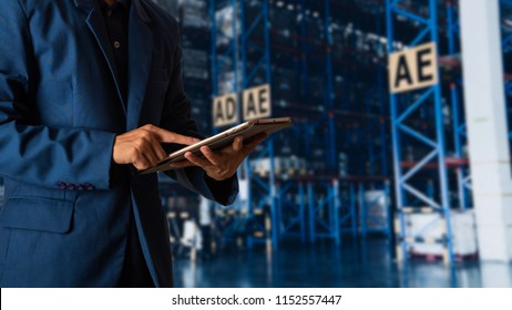 Businessman manager using tablet check and control for workers with Modern Trade warehouse logistics. Industry 4.0 concept