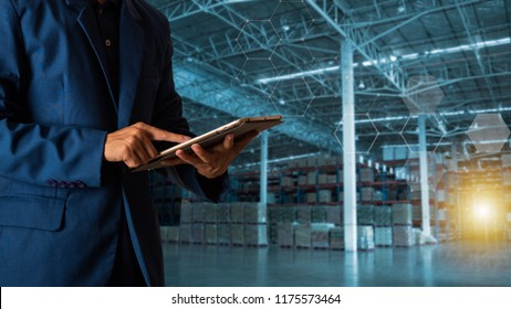 Businessman manager using tablet check and control for workers with Modern Trade warehouse logistics. Industry 4.0 concept,planning of logistics, Transportation within the country and Global.