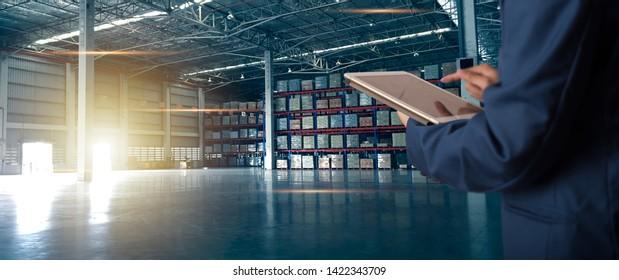Geschäftsmann-Manager mit Tablet-Check und-Kontrolle für Mitarbeiter mit moderner Warenlager-Logistik. Industriekonzept 5.0