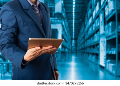 Businessman manager using tablet check and control for workers with Modern Trade warehouse logistics. Industry 5.0 concept