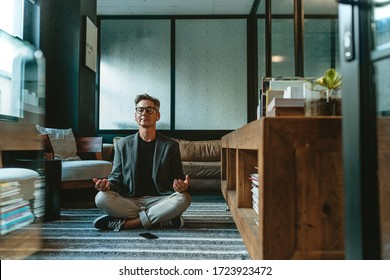 Businessman meditating in lotus pose on the floor in the office. Mature business professional doing yoga meditation in office lounge.