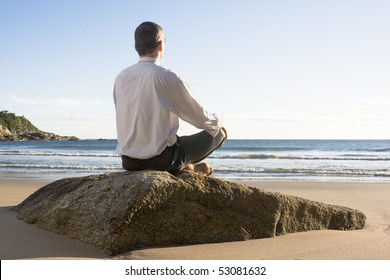 Businessman meditating on a sunny beach in the morning