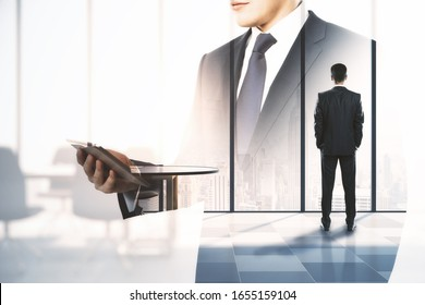 Businessman in meeting room with double exposure of businessman using digital tablet. Business and teamwork concept.