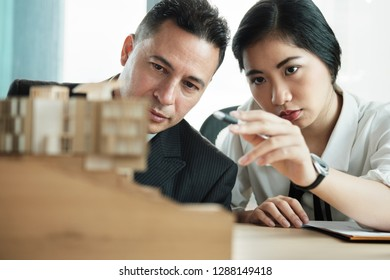 Businessman at meeting in room looking at wooden miniature model of architecture and design project. Client evaluating real estate investment
