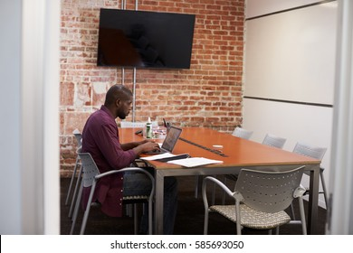 Businessman In Meeting Room Working On Laptop
