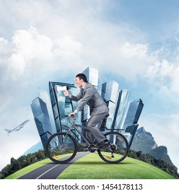 Businessman with megaphone in hand on bike. Corporate employee announcing in loudspeaker. Man in business suit riding bicycle on road and world round panorama of modern megapolis with high skyscrapers