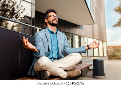 Businessman - mentally preparing for business meeting. Sitting in meditation pose in front of office building and smiling