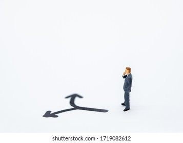 Businessman miniature people figure thinking and looking to direction left or tight arrow on white background with copy space using for business,marketing and financial concept.