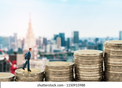 Businessman miniature standing on stack and tokyo city skyline background