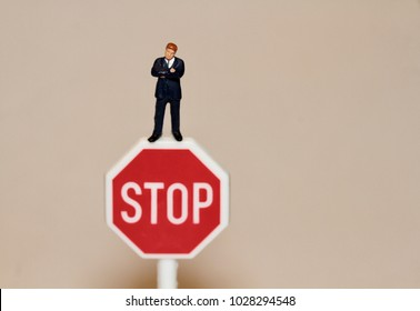 businessman in miniature and a stop sign