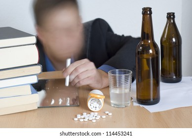Businessman mixing alcohol, pills and cocain in the office. Blurry motion effect.