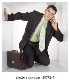 businessman with mobile and briefcase in the cramped white cube