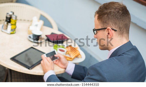 Businessman with mobile phone during breakfast.