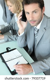 Businessman with mobile telephone and note pad