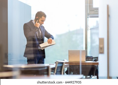 Businessman in modern corporate office, holding financial newspaper, talking on a mobile phone while looking what time is it at his wristwatch.