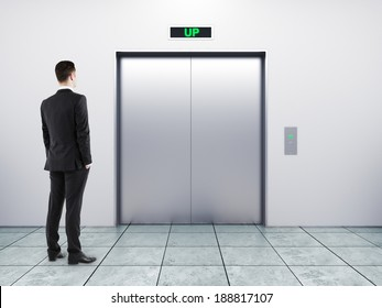 businessman and modern elevator with closed doors
