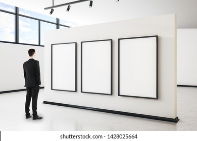 Businessman in modern gallery interior with city view, empty poster and daylight. Mock up,