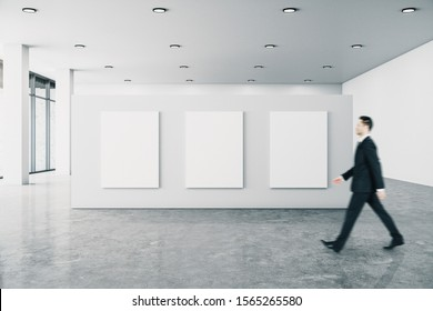Businessman in modern gallery interior with empty billboard and shadows, city view and daylight. Mock up,
