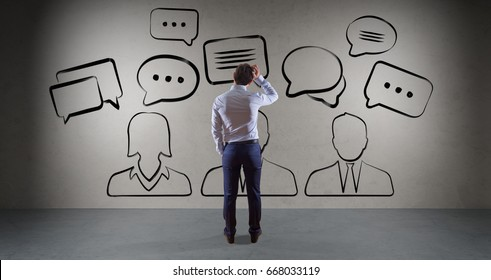 Businessman in modern interior watching discussion icons sketch on a wall 3D rendering